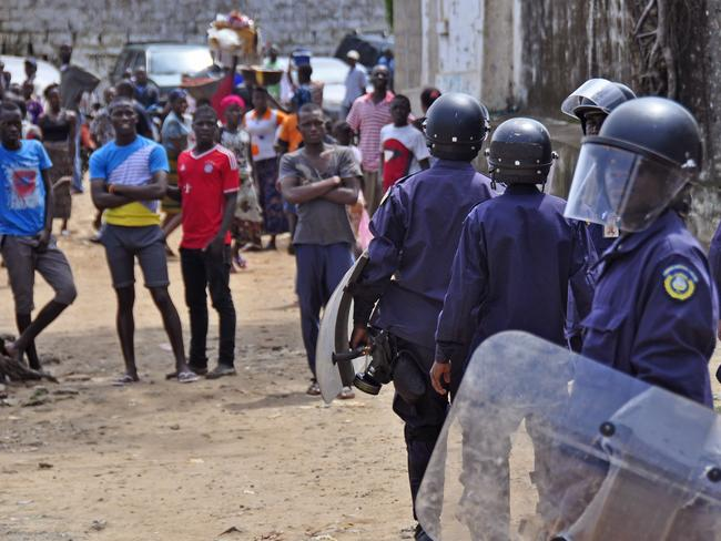 Stand off ... Liberian policemen dressed in riot gear disperse protesters who blocked a main road after the body of someone suspected of dying from the Ebola virus was not removed by health workers in Monrovia, Liberia. Picture: AP
