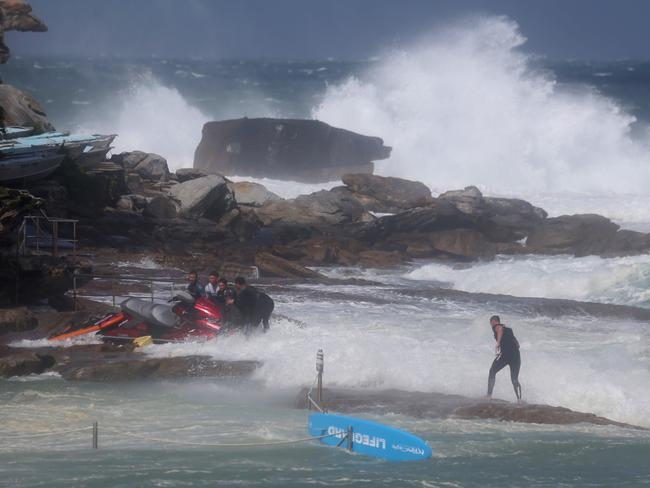 A rescue board joins the jet ski on the rocks as lifeguards struggle to move the craft. Picture: John Grainger