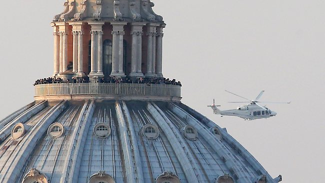 ROME, ITALY - FEBRUARY 28: People crowd the gallery on top of St Peter's Basilica as a helicopter carrying Pope Benedict XVI passes by on its way out of Vatican City on February 28, 2013 in Rome, Italy. The Pontiff is flying to Castel Gandolfo where he will cease to be Pope at 8:00pm local time. Pope Benedict XVI has been the leader of the Catholic Church for eight years and is the first Pope to retire since 1415. He will stay at the Papal Summer residence of Castel Gandolfo until renovations are complete at a monastery in the grounds of the Vatican and will be known as Roman pontiff emeritus or pope emeritus. (Photo by Peter Macdiarmid/Getty Images)