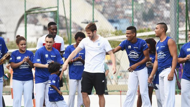 Adam Lallana of England is invited to take part in Capoeira.