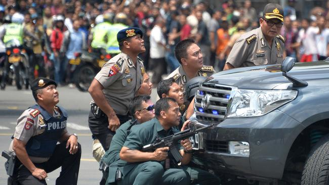 Targeted ... Indonesian police take position behind a vehicle as they pursue suspects after a series of blasts in Jakarta.