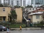 People walk past a building where the roof was blown off by Hurricane Irma on September 10, 2017 in Miami, Florida. Hurricane Irma, which first made landfall in the Florida Keys as a Category 4 storm on Sunday. Picture: Joe Raedle/Getty Images/AFP