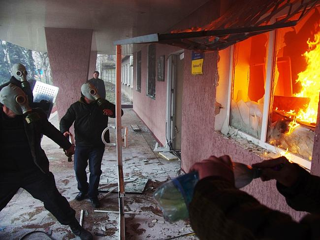 Pro-Russia protester wearing gas masks storm a regional police building as one prepares a petrol bomb in the eastern Ukrainian city of Horlivka.