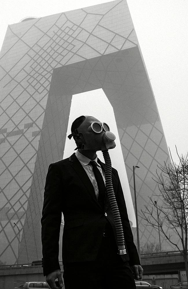 Unusual style ... The groom poses in his wedding outfit and gas mask in downtown Beijing during this week's smog crisis. Picture: Austral. Source: Supplied.