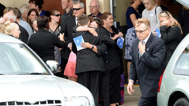 Friends and relatives comfort each other at the funeral.