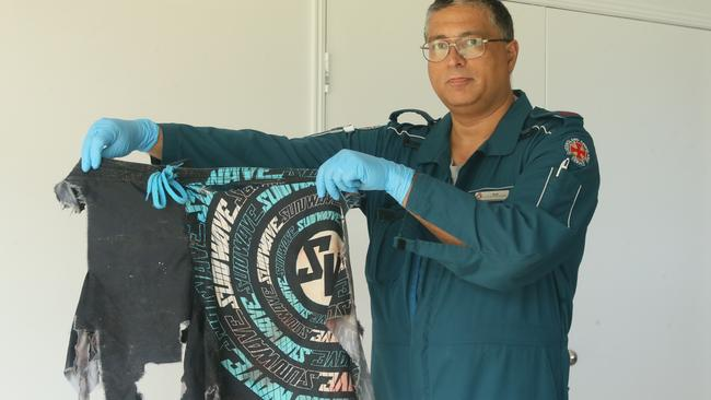 The ripped clothes of dingo attack victim Dane Allan are held up by paramedic Rod Macdonald. Pic: Glenn Barnes