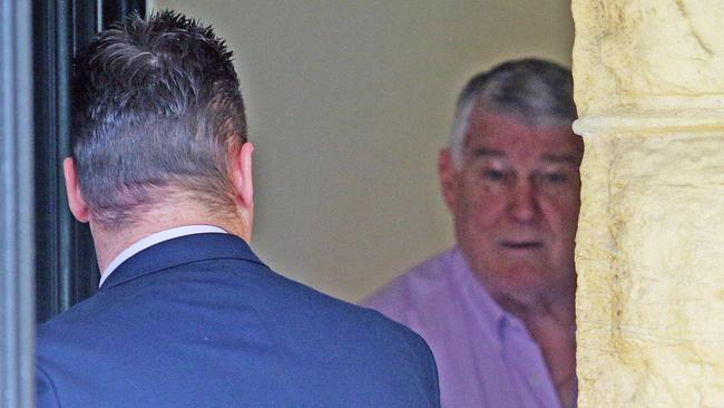 Wayne Beavis (right) speaks with a detective at his home as the raid unfolds. Picture: Carly Earl