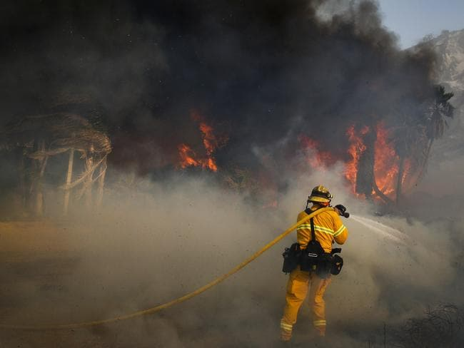 A firefighter battles a wildfire at Faria State Beach in Ventura, California. The windswept blazes have forced tens of thousands of evacuations and destroyed dozens of homes. Picture: AP Photo/Jae C. Hong