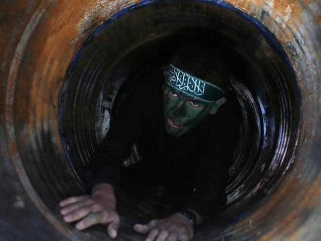 A Palestinian youth crawls in a tunnel during a graduation ceremony for a training camp run by the Hamas movement on January 29, 2015 in Khan Yunis, in the southern Gaza Strip.