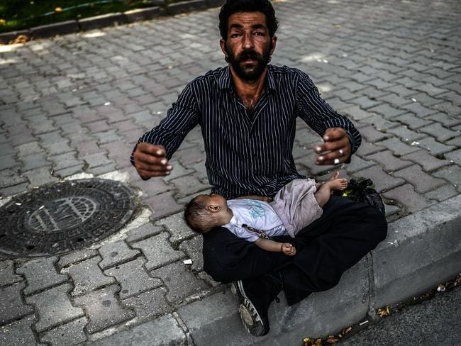 A Syrian refugee man gestures as he begs in the street with a baby lying on his lap in Istanbul on June 19, 2014. Picture: AFP