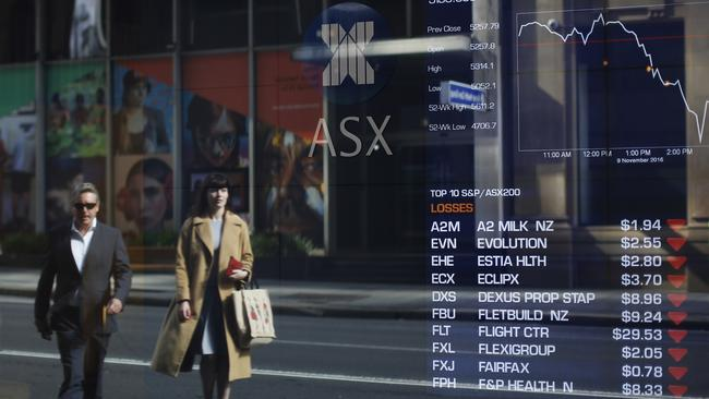 Pedestrians are reflected against an electronic board displaying stock information inside the Australian Securities Exchange in Sydney. (David Moir/Bloomberg)