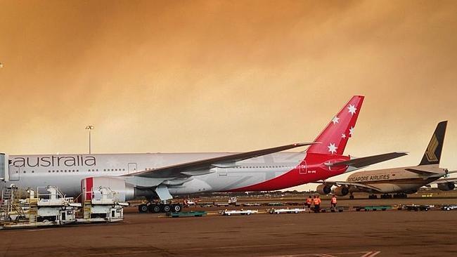 A thick cloud of orange smoke covers Sydney Airport. (Photo: Adam Yaglipinar)