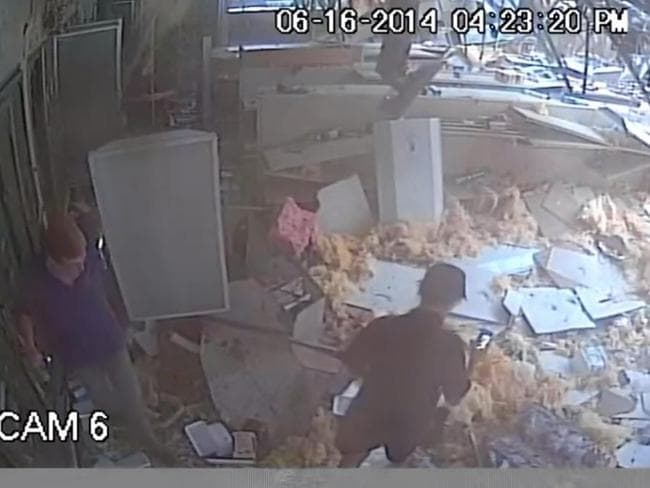 Carnage ... Workers enter the shop to assess the destruction caused. Picture: Web grab / YouTube