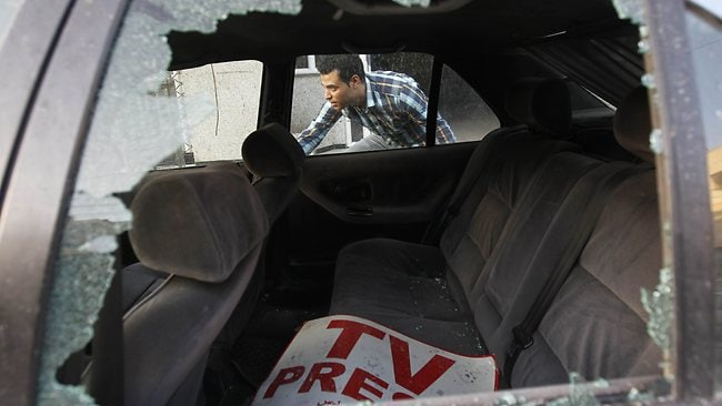 A Palestinian journalist inspects his work car in Gaza City on Sunday. Picture: AFP