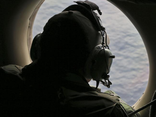 Flight officer Rayan Gharazeddine, on board a Royal Australian Air Force AP-3C Orion, scans for the missing Malaysia Airlines Flight MH370 in the southern Indian Ocean. Picture: AP Photo/Rob Griffith