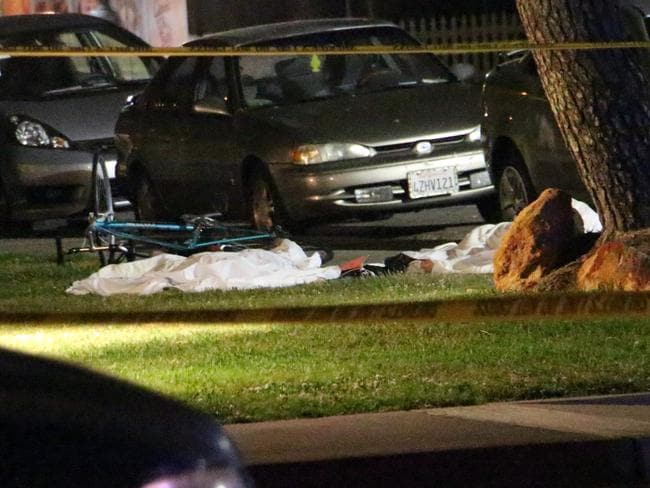 Mass shooting ... bodies are seen covered on the ground after the mass drive-by shooting. Picture: AP Photo/KEYT, John Palminteri