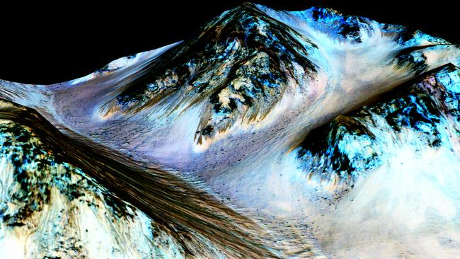 These dark, narrow, 100m-long streaks called recurring slope lineae flowing downhill on Mars are believed to have been formed by contemporary flowing water. Picture: NASA/JPL/University of Arizona