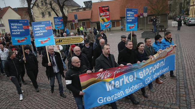 Protestors with a banner reading: 'Stop Merkel! Secure borders, drop the CDU!'. Picture: Sean Gallup
