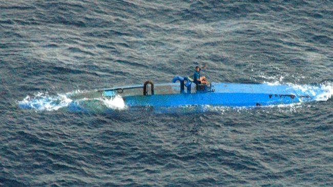 Suspected narcotic drug smuggler perched atop a semi-submersible submarine after being spotted by USA Customs authorities off the coast of Central America. Picture: US Coast Guard