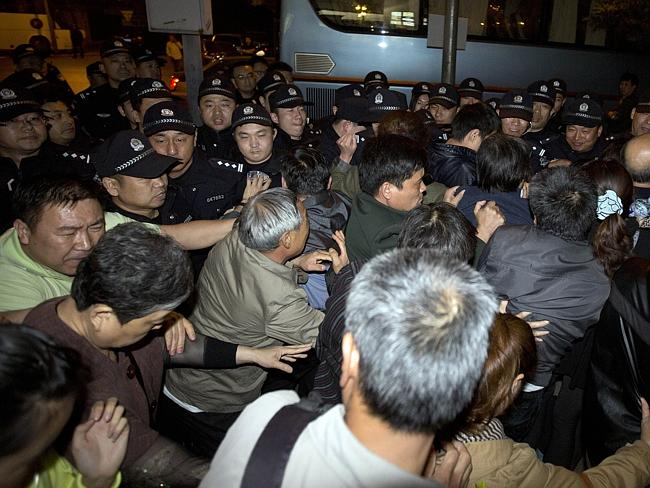 Fury ... Relatives of Chinese passengers on-board the Malaysia Airlines MH370 push through a police line to march to the Malaysian embassy from a hotel in Beijing. Picture: AP