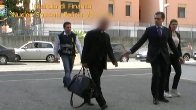 This image from a video released by the Guardia di Finanzia Italian police on June 28, 2013 shows Nunzio Scarano (front-L) escorted by policemen after being arrested the same day in Rome. (Picture: AFP PHOTO)