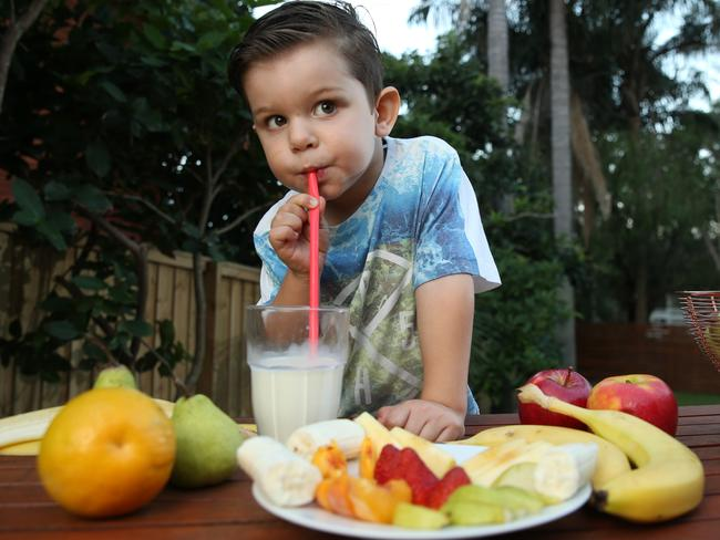 Now this is a healthy breakfast. Zack, 3, tucks into fruit and milk to start his day. Picture: Tim Hunter