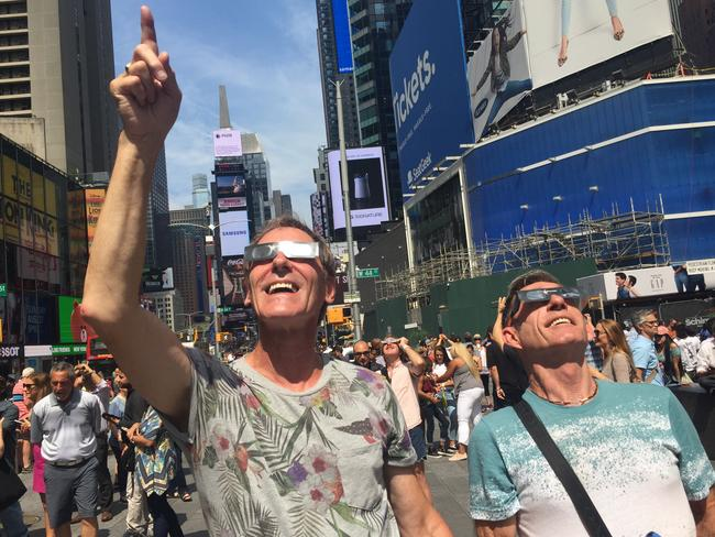 Canadians Barry Robison and David Stafford marvel at the celestial event in Times Square. Picture: James Law/news.com.au
