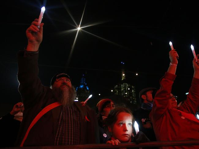Members of the public hold candles to mourn the victims of HIV/AIDS and the victims of flight MH17 during a candlelight vigil at Federation Square. At least six delegates travelling to the 20th International AIDS Conference were on board the Malaysia Airlines flight MH17. Picture: Getty