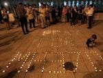 "A girl lights a candle next to a message reading ""Pray for MH370"". Picture: AP"