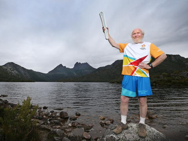 Paul Darby holds the Queen's Baton aloft at Cradle Mountain. Picture: CHRIS KIDD