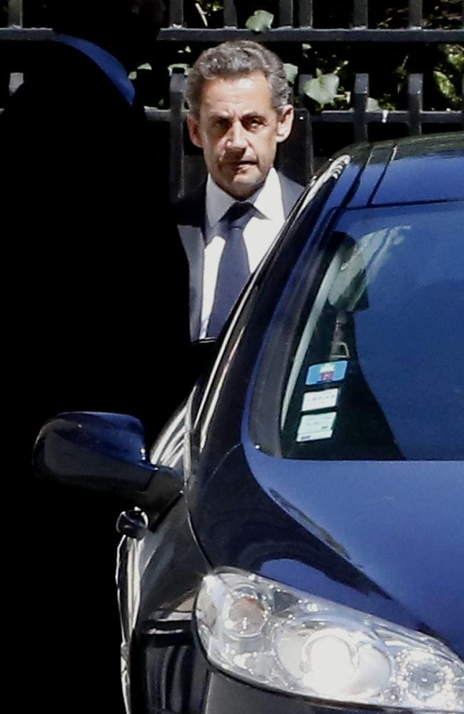 Grim-faced ... Nicolas Sarkozy leaving his house in Paris on Wednesday.