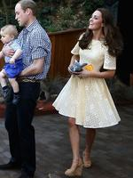 In a lemon-tinged Rebecca English frock Catherine, Duchess of Cambridge picks up a toy bilby Prince George of Cambridge threw on the ground as Prince William, Duke of Cambridge holds Prince George of Cambridge during a visit to the Bilby Enclosure at Taronga Zoo. Picture: Getty