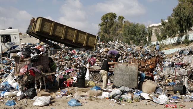 Municipal employees dump waste rubbish collected from the streets in the centre of Gaza City.