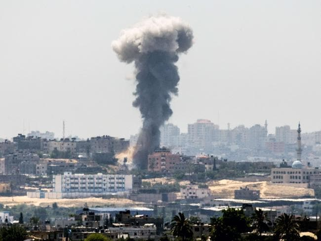 A picture taken from the southern Israeli Gaza border shows smoke billowing from buildings following an Israeli air strike in Gaza City, on July 10. Pic: JACK GUEZ