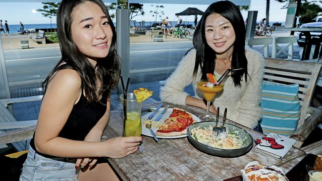 Tiffany Shih from Taiwan and Esther Tsang from Hong Kong enjoy a meal at the Surfers Paradise Beach Cafe. Picture: Luke Marsden/News Corp Australia.
