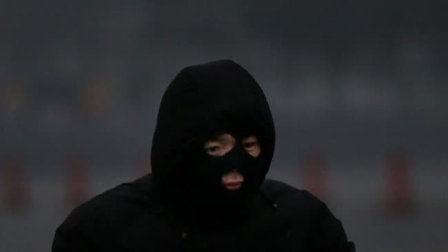 A man wearing the headgear rides a bicycle during severe pollution on January 30, 2013 in Beijing, China.