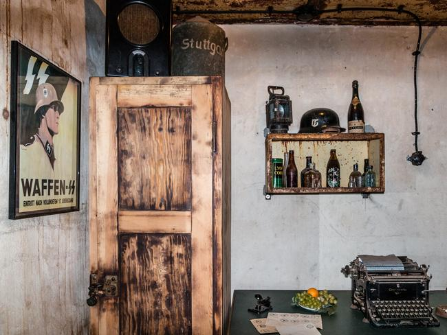 An old office is seen with a typewriter, bottles of alcohol and a portrait of a Waffen-SS soldier. Picture: Solveig Grothe/Spiegel Online