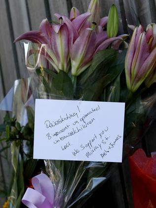 """Devastating, we support you"". Flowers line the footpath."
