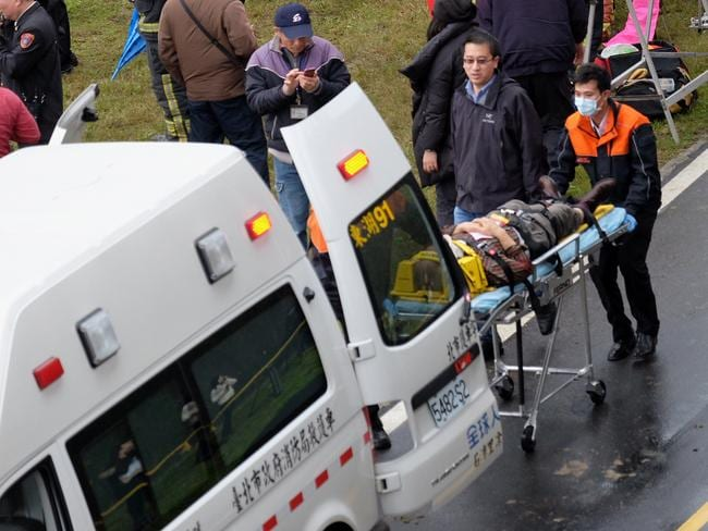 On the scene ... rescue personnel put an injured passenger into an ambulance. Picture: AFP