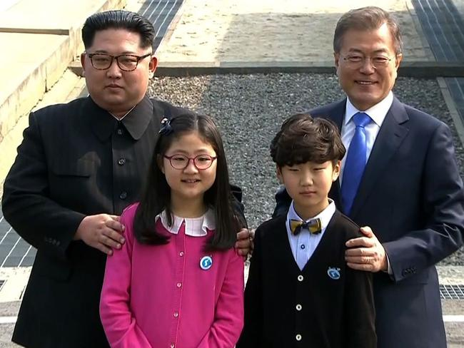 The Korean leaders pose with children as they meet at the Military Demarcation Line that divides their countries at Panmunjom. picture: Korean Broadcasting Service/AFP