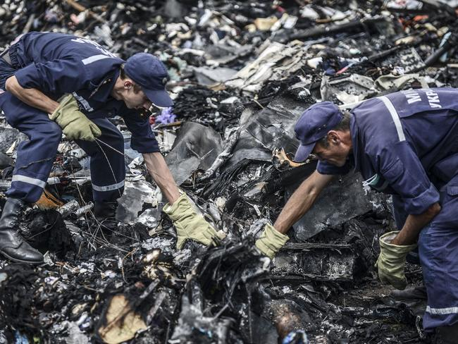 Horror scene ... Ukrainian State Emergency Service employees search for bodies among the wreckage at the crash site of Malaysia Airlines Flight MH17. Picture: Bulent Kilic