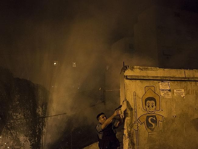 Smoke and panic on the streets ... an officer of the Pacifying Police Unit takes aim. Picture: Felipe Dana