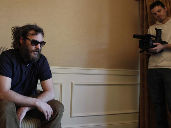 Joaquin Phoenix, left, poses for a portrait as Casey Affleck films for I'm Still Here. Picture: AP
