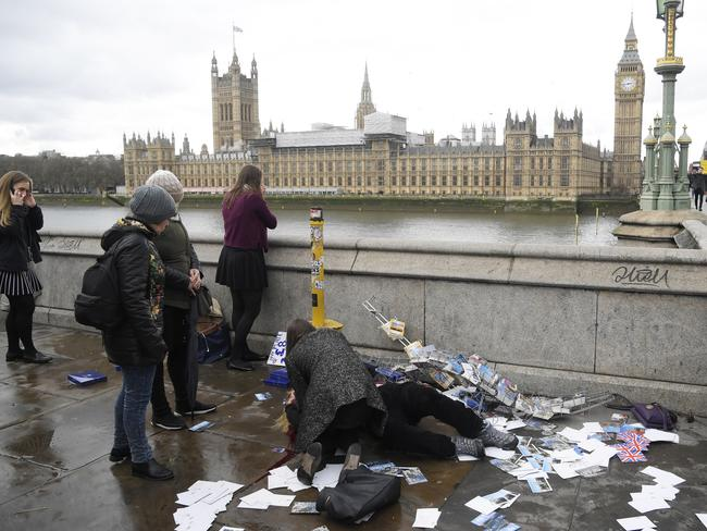 An injured woman is assisted on Westminster Bridge in London. Picture: Reuters