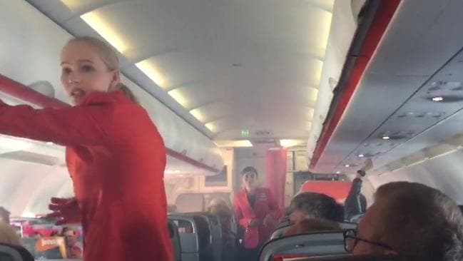 Cabin staff deal with the smoke on the Sydney to Cairns flight that was diverted to Brisbane.