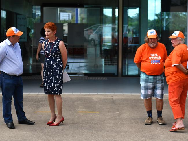 One Nation Leader Senator Pauline Hanson (second left) speaks with candidate Neil Symes (left) at a polling station in Masfield, south of Brisbane while campaigning for the Queensland election. Picture: Mick Tsikas/AAP
