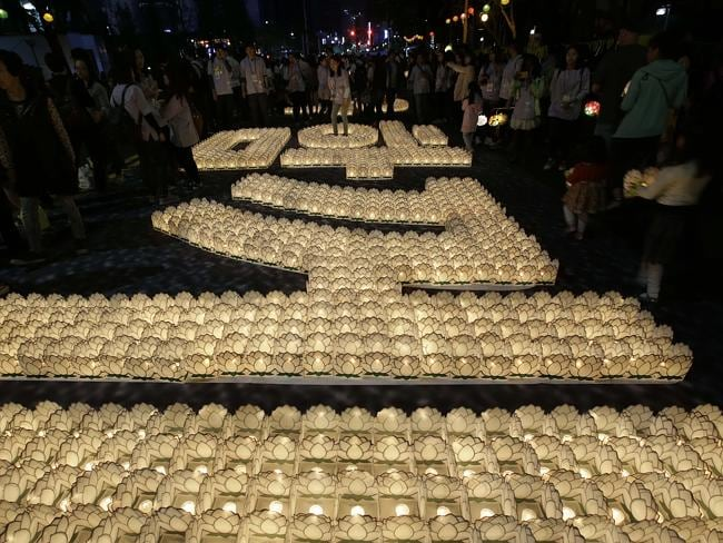 "Prayers ... South Korean Buddhists put candles to form the words meaning ""Together"", for cherishing the memory of deceased persons and safe return of passengers aboard the sunken ferry, on a street in Seoul."