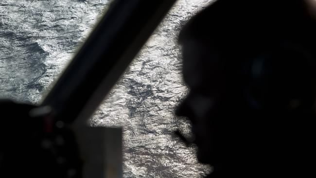 Captain Peter Moore is silhouetted against the southern Indian Ocean aboard a Royal Australian Air Force AP-3C Orion aircraft searching for the missing Malaysian Airlines flight MH370.