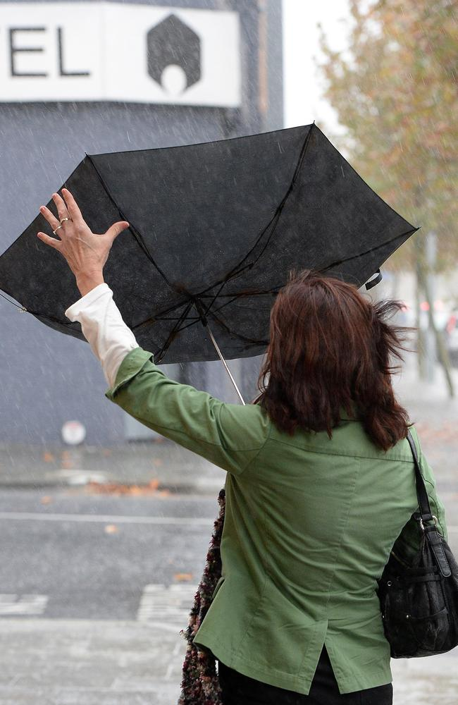 A woman grapples with her umbrella during the downpour yesterday. Picture: Daniel Wilkins.