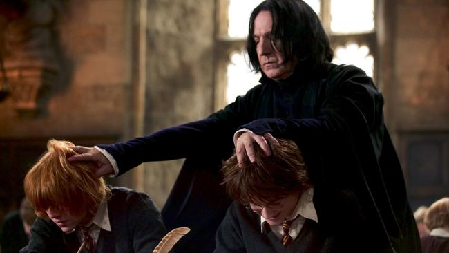 Alan Rickman as Severus Snape grabbing the heads of Rupert Grint as Ron Weasley and Daniel Radcliffe as Harry Potter.